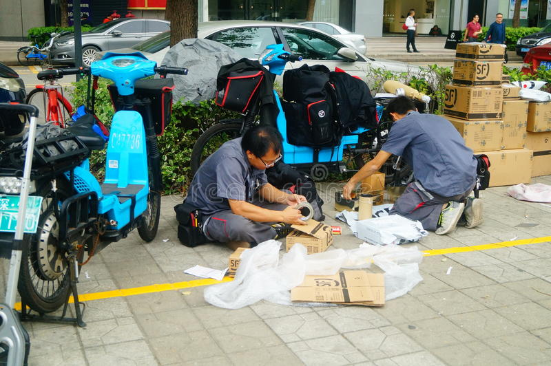 Shenzhen, China: on the sidewalk courier company employees are distributing customer courier stock images