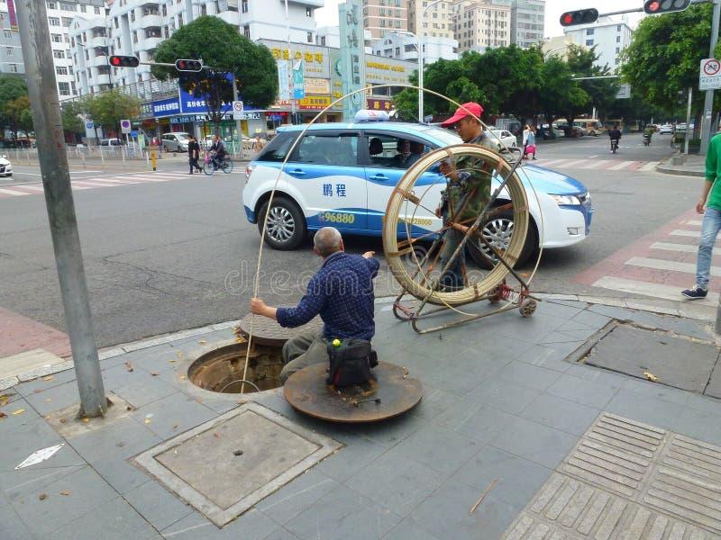 Shenzhen, China: trabalhadores do saneamento para cancelar o esgoto fotos de stock royalty free
