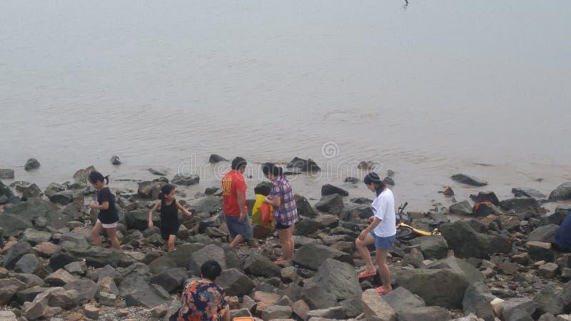 Shenzhen, China: vrouwen en kinderenspel bij de strand of vangstkrabben royalty-vrije stock afbeelding