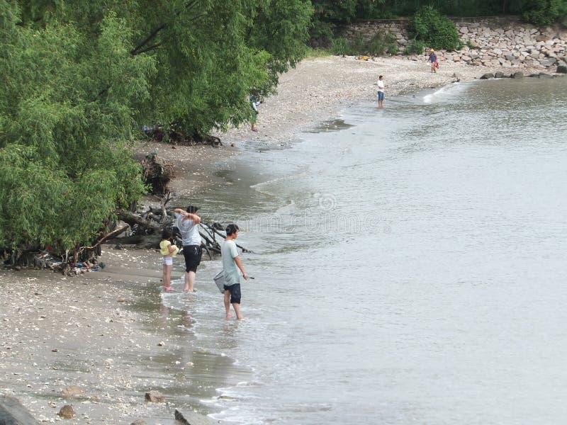Shenzhen, China: vrouwen en kinderenspel bij de strand of vangstkrabben royalty-vrije stock afbeeldingen