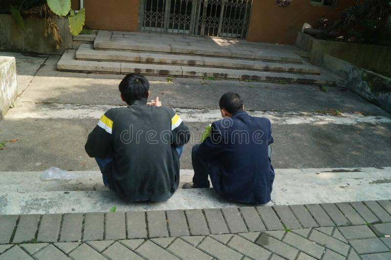 Shenzhen, China: Workers in eating fast food. Shenzhen Overseas Chinese Town Scenic, two workers are eating fast food, outdoors royalty free stock photo