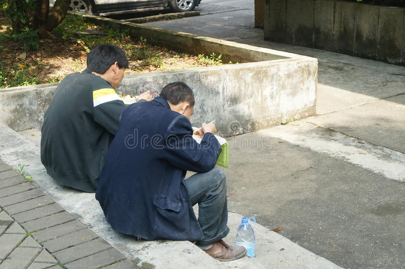 Shenzhen, China: Workers in eating fast food. Shenzhen Overseas Chinese Town Scenic, two workers are eating fast food, outdoors stock image
