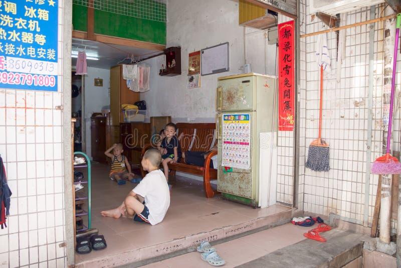 SHENZHEN, CHINE, 2011-07-24 : Enfants chinois dans le hall de leur maison dans le secteur pauvre de la ville image stock