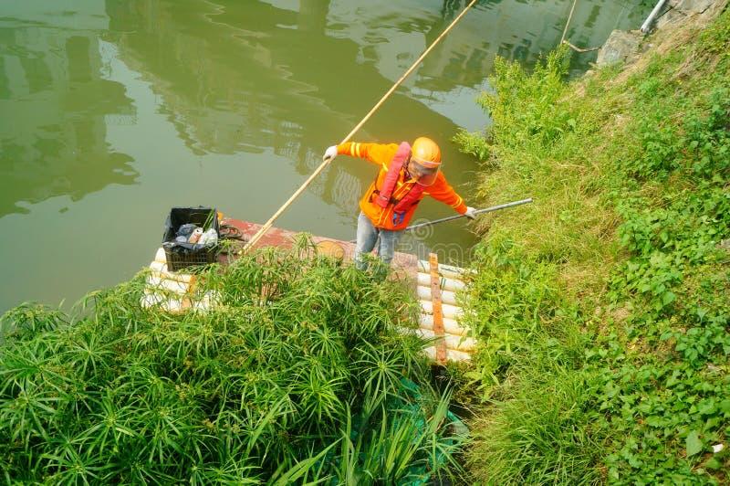 Shenzhen, Cina: i lavoratori puliscono lo spreco di plastica su un fiume fotografie stock