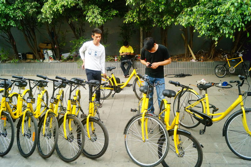 Shenzhen, Cina: i lavoratori riparano le bici comuni fotografie stock
