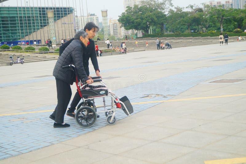 Shenzhen, Cina: le donne anziane in sedie a rotelle praticano camminare immagine stock