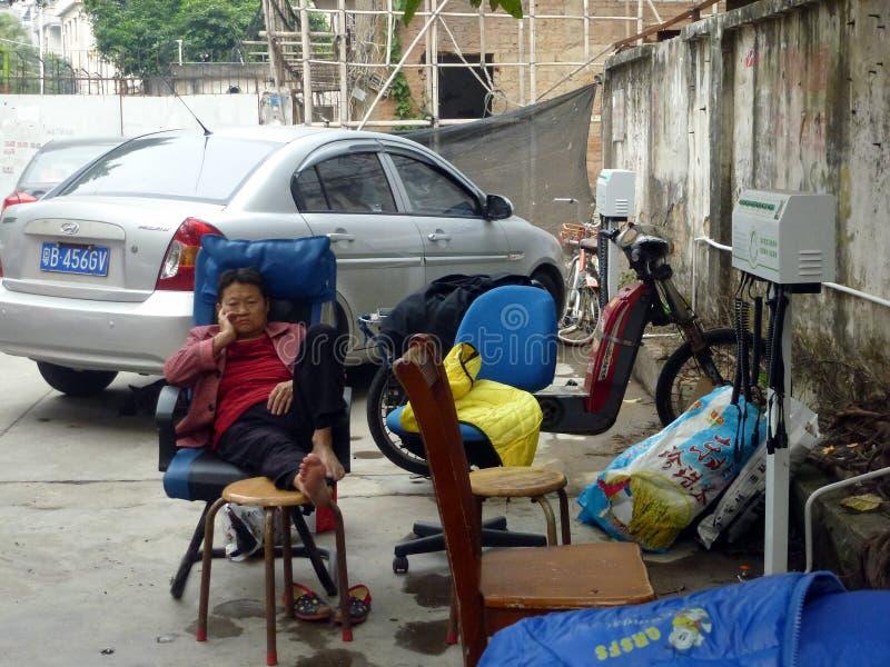 Shenzhen, Cina: un parrucchiere del bordo della strada, una donna nello svago immagine stock