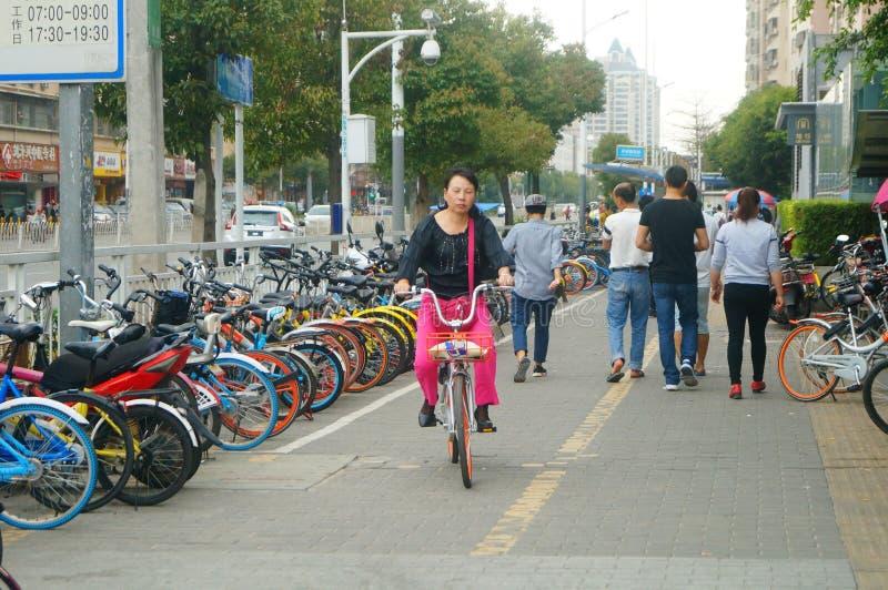 Shenzhen Kina: cykla kvinnor på gatorna royaltyfri foto