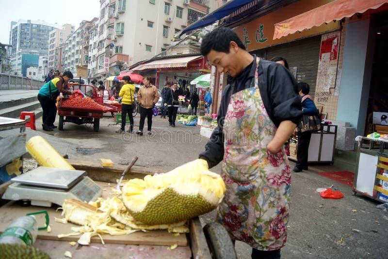 Shenzhen Kina: försäljare som säljer jackfruiten royaltyfria foton