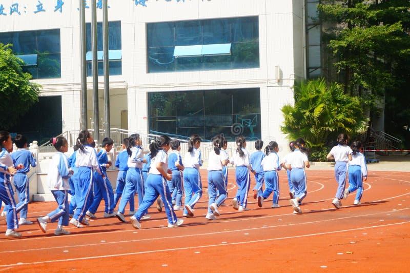 Shenzhen Kina: grundskola för barn mellan 5 och 11 årstudenter har grupper för fysisk utbildning arkivbild
