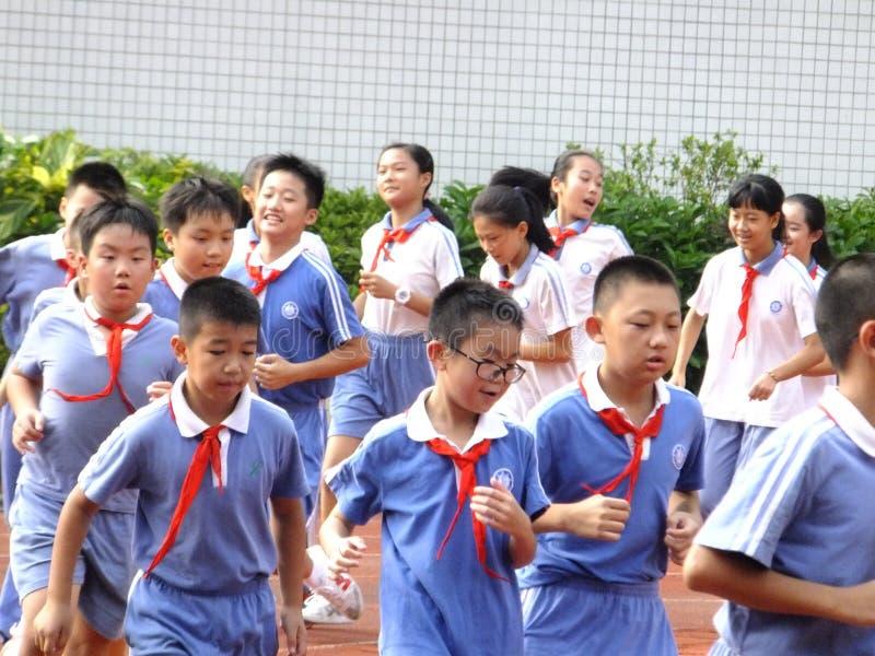 Shenzhen Kina: grundskola för barn mellan 5 och 11 årstudenter i gruppen för fysisk utbildning arkivfoton