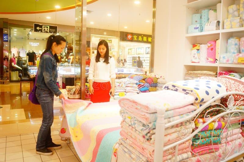 Shenzhen Kina: kvinnor köper sängkläder och annan sängkläder royaltyfri foto