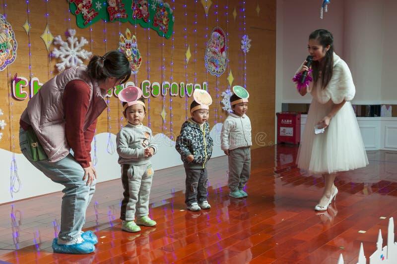 SHENZHEN KINA, 2011-12-23: lärare och förälder som spelar med ungen royaltyfria foton