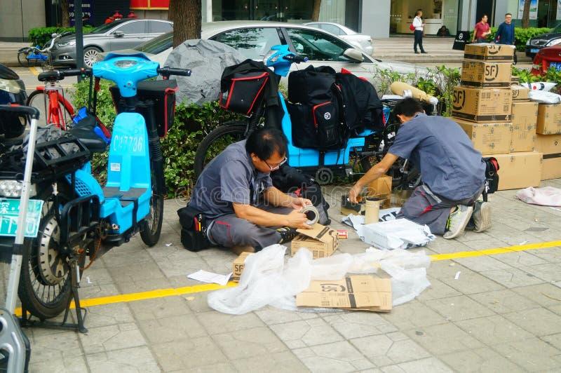 Shenzhen Kina: på trottoarkurirföretaget fördelar anställda kundkuriren arkivbilder