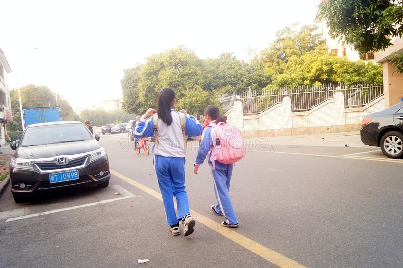 Shenzhen Kina: två grundskola för barn mellan 5 och 11 årflickor går hem på deras väghem från skola royaltyfri bild