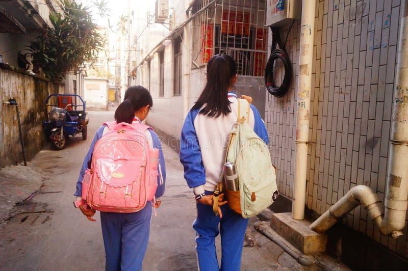 Shenzhen Kina: två grundskola för barn mellan 5 och 11 årflickor går hem på deras väghem från skola royaltyfri fotografi