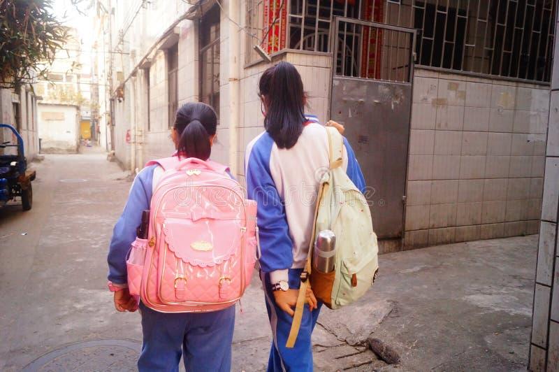 Shenzhen Kina: två grundskola för barn mellan 5 och 11 årflickor går hem på deras väghem från skola arkivfoto