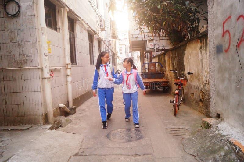 Shenzhen Kina: två grundskola för barn mellan 5 och 11 årflickor går hem på deras väghem från skola arkivbilder