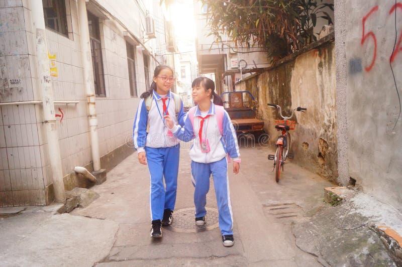 Shenzhen Kina: två grundskola för barn mellan 5 och 11 årflickor går hem på deras väghem från skola fotografering för bildbyråer