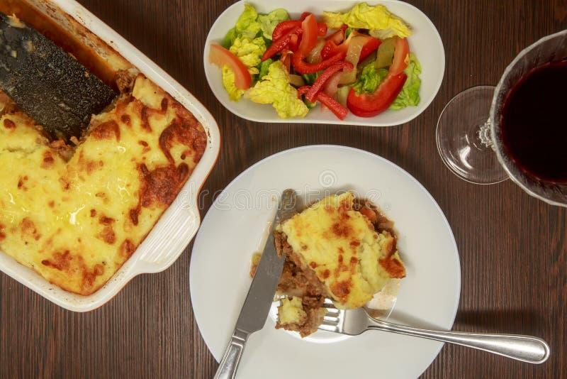 Shepherd пирог ` s с салатом, красным вином стоковая фотография