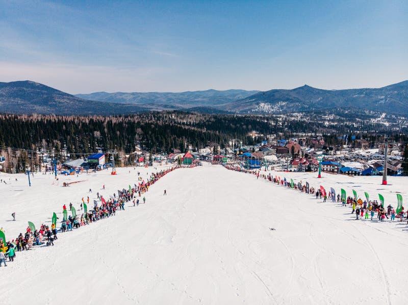 Sheregesh, περιοχή Kemerovo, της Ρωσίας - 13 Απριλίου 2019: Αναβάτες σκι και σνόουμπορντ φεστιβάλ Grelka στο μπικίνι Εναέρια φωτο στοκ εικόνες