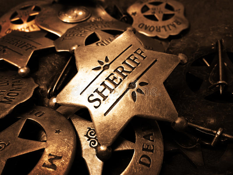 Sheriff's Badge Tin Star Law Enforcement. Sheriff's tin badge in pile of star law enforcement badges stock image