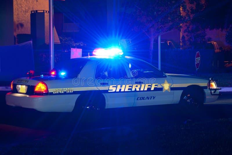 Sheriffauto bij nacht met lichten  stock afbeelding