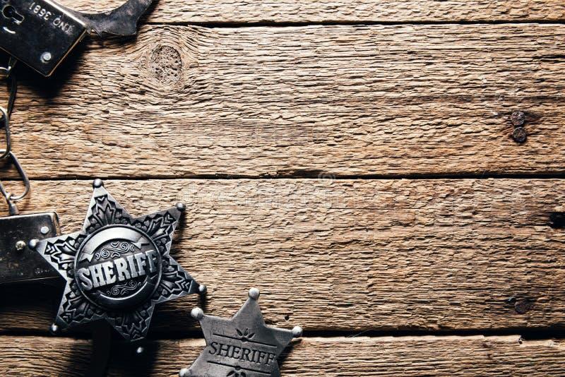 Sheriffstjärna och handbojor på trätabellen arkivfoton