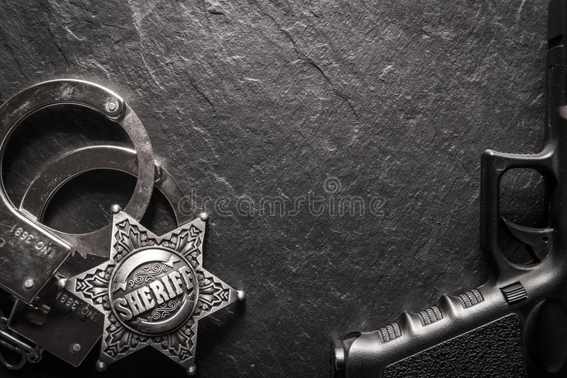 Sheriffstjärnan och handbojor på svart kritiserar tabellen royaltyfri fotografi