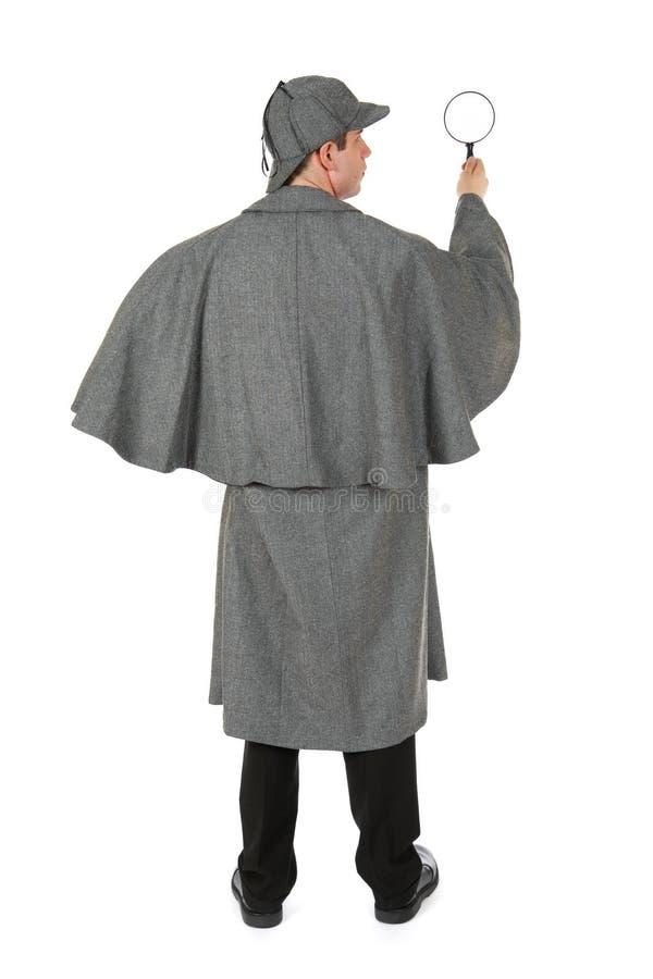 Sherlock: Вид сзади человека задерживая лупу стоковая фотография rf