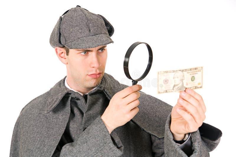 Sherlock: Любознательный сыщик смотрит деньги с лупой стоковые фото