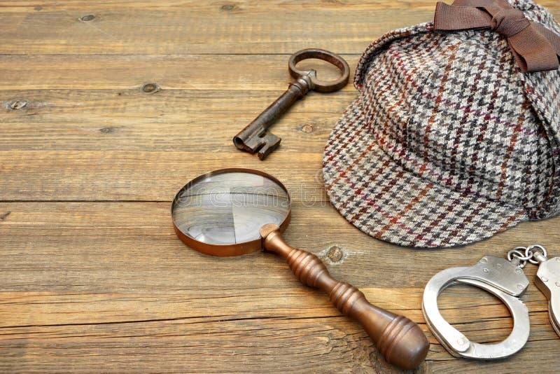 Sherlock Holmes Cap famous as Deerstalker, Key, Handcuffs and Ma. Sherlock Holmes Cap famous as Deerstalker, Old Key, Real Handcuffs and Vintage Magnifying Glass stock photos
