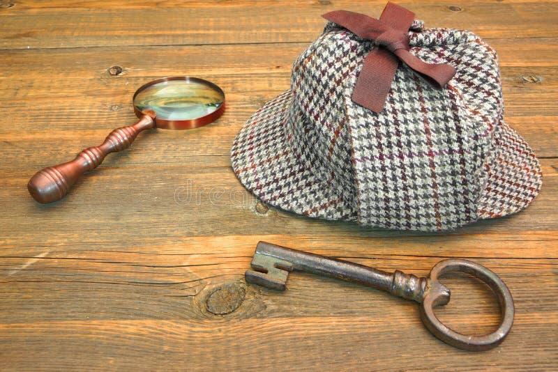 Sherlock Holmes Cap famous as Deerstalker, Old Key and Magnifier. Sherlock Holmes Cap famous as Deerstalker, Old Key and Retro Magnifier on Grunge Wooden Table royalty free stock image