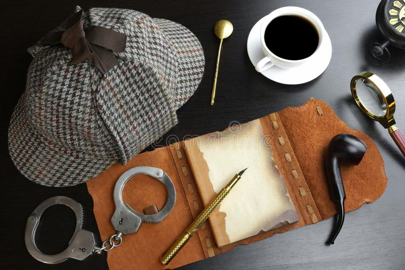 Sherlock Holmes Concept. Private Detective Tools. On The Black Wood Table Background. Deerstalker Hat, Opened Notebook With Blank Brown Page, Pipe, Magnifying royalty free stock images