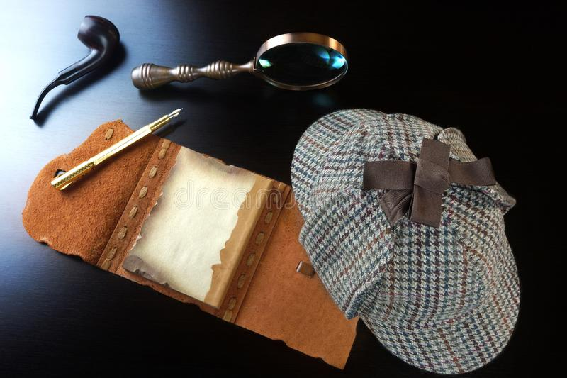 Sherlock Holmes Concept. Private Detective Tools. On The Black Wood Table Background. Deerstalker Hat, Opened Notebook With Blank Brown Page, Pipe, Magnifying stock photography