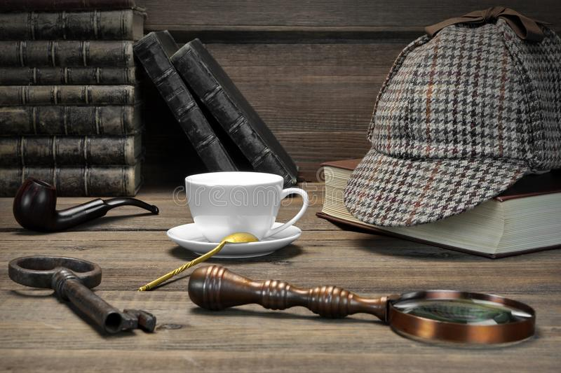 Sherlock Holmes Concept. Private Detective Tools On The Wood Tab. Le Background. Deerstalker Cap, Magnifier, Key, Cup, Notebook, Smoking Pipe royalty free stock photography