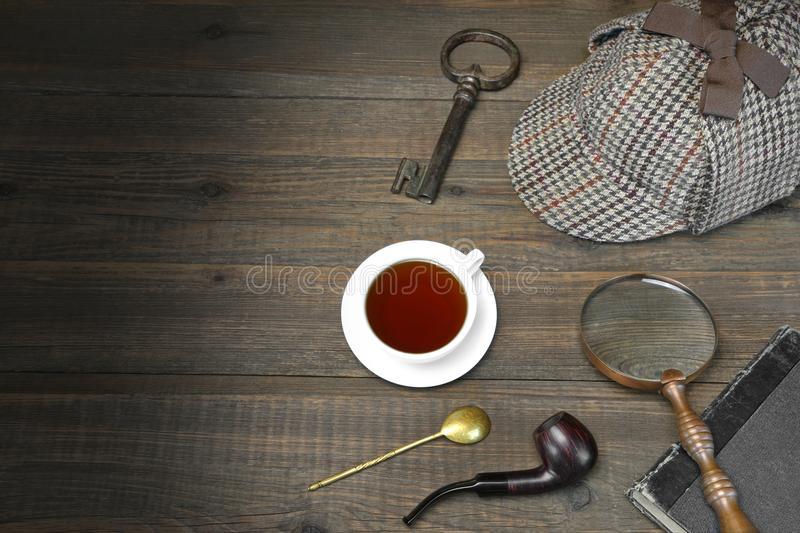 Sherlock Holmes Concept. Private Detective Tools On The Wood Tab. Le Background. Deerstalker Cap, Magnifier, Key, Cup, Notebook, Smoking Pipe stock image