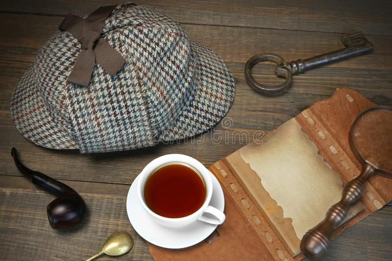 Sherlock Holmes Concept. Private Detective Tools On The Wood Tab. Le Background. Deerstalker Cap, Magnifier, Key, Cup, Notebook, Smoking Pipe stock photo