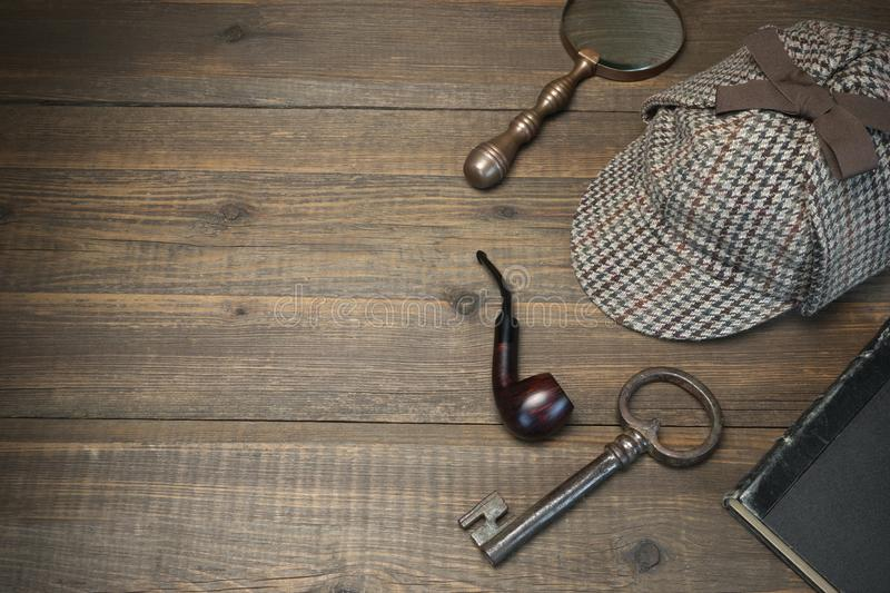 Sherlock Holmes Concept. Private Detective Tools On The Wood Tab. Le Background. Deerstalker Cap, Old Key And Book, Tobacco Pipe, Vintage Magnifying Glass royalty free stock photo