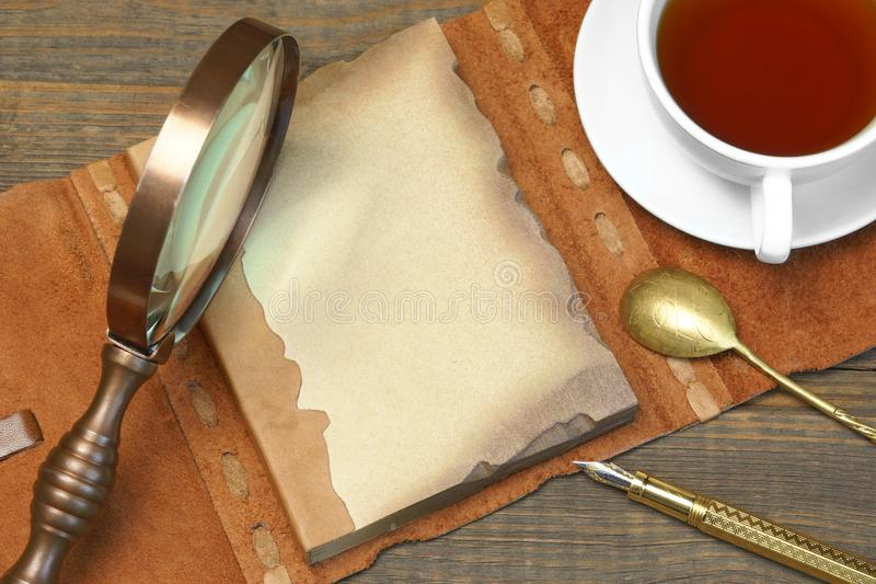 Sherlock Holmes Concept. Private Detective Tools On The Wood Tab. Le Background. Magnifying glass, Tea Cup, Notebook With Blank Brown Page, Pen royalty free stock image