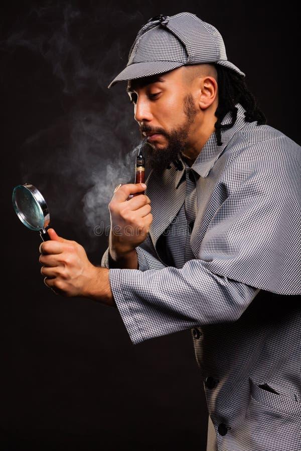 Sherlock Holmes med röret och förstoringsglaset arkivfoton