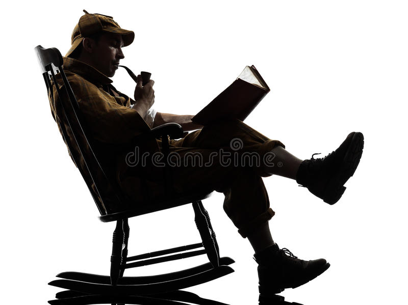 Sherlock holmes reading silhouette. Sitting in rocking chair in studio on white background royalty free stock photo