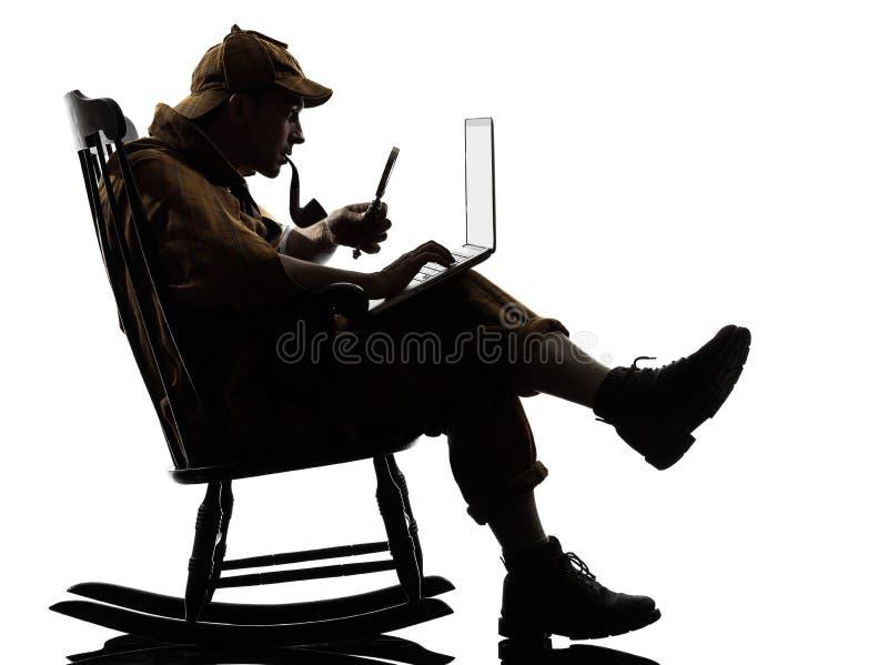 Sherlock holmes silhouette computing. Sherlock holmes with computer laptop silhouette sitting in rocking chair in studio on white background stock photography