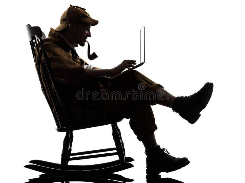 Sherlock holmes silhouette computing. Sherlock holmes with computer laptop silhouette sitting in rocking chair in studio on white background royalty free stock photo