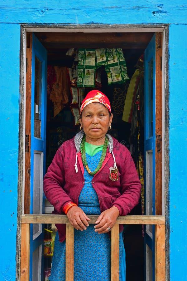 Sherpa-Frau in der traditionellen Kleidung, die an der vorderen blauen Tür steht stockbild