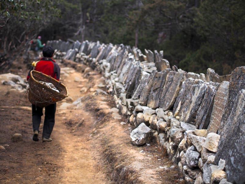 Sherpa Porter Walking på slinga bredvid tibetana Mani Stones royaltyfria bilder