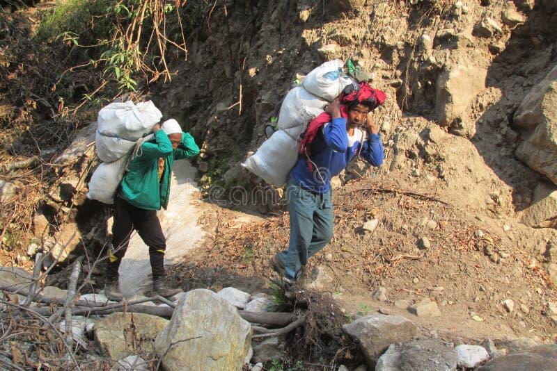 Sherpa-Träger tragen Korb im Nepal-Trekkingsweg stockbilder