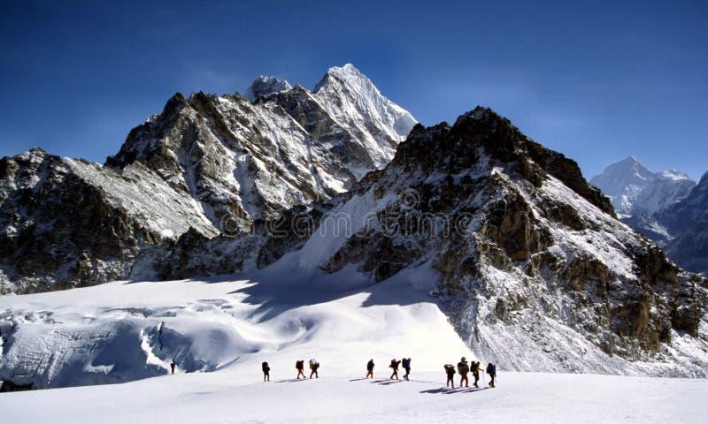Sherpas, das einen Himalayam Gletscher kreuzt stockbilder