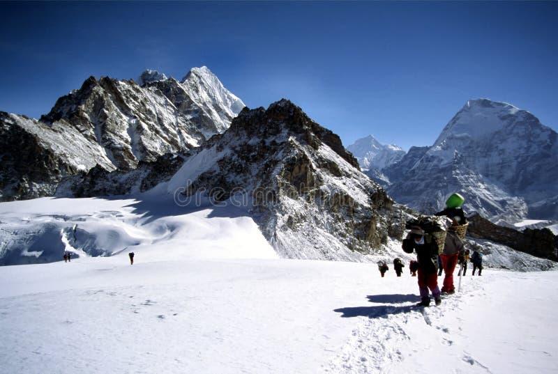 Sherpas y escaladores que cruzan un glaciar de Himalayam imagen de archivo