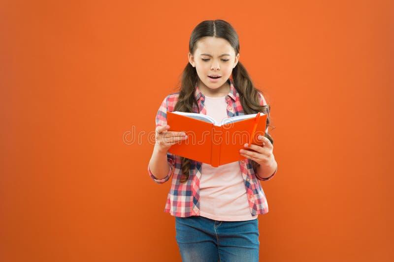 Shes μια αληθινή βιβλιόψειρα Λατρευτό μικρό βιβλίο ανάγνωσης παιδιών στο πορτοκαλί υπόβαθρο Χαριτωμένη ανάγνωση μικρών κοριτσιών  στοκ φωτογραφία με δικαίωμα ελεύθερης χρήσης